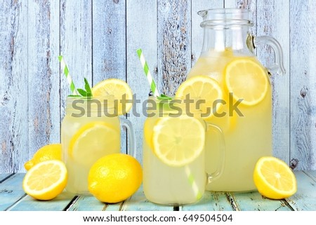 Vintage pitcher of lemonade with two mason jar glasses and lemons on rustic blue wood background