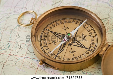 vintage pocket brass compass opened over topographical map - stock photo