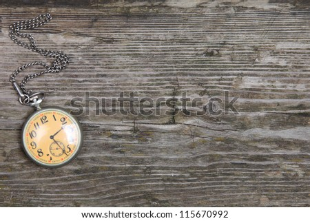 Vintage pocket watch on chain on wooden background - stock photo