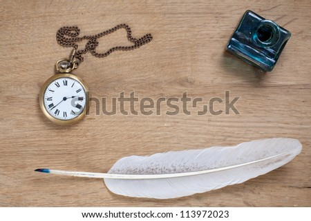 Vintage pocket watch, quill and inkwell on wood