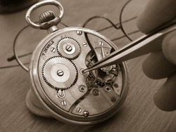 vintage pocket watch under repair, exposed mechanism and watchmaker taking small gear with tweezers