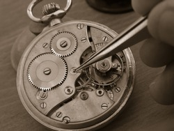 vintage pocket watch under repair, with exposed mechanism, watchmaker taking a small gear with tweezers