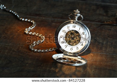 Vintage pocket watch with open lid and chain on wooden surface