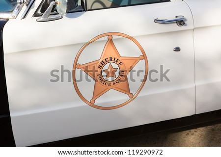Vintage police car with detail focus on door and reflections of warning lights in paint