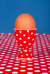 Vintage polka dot egg cup with a boiled egg on the red and white polka dot table. Retro background for design. Polka dot pattern. Copy space for the text editing