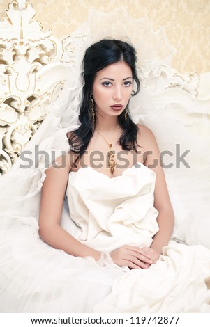 Vintage portrait of a beautiful queen like girl (bride) in the white bedroom. Retro style. Studio shot