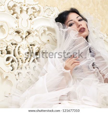 Vintage portrait of a beautiful queen like girl (bride) in the white bedroom. Retro style. Studio shot - stock photo