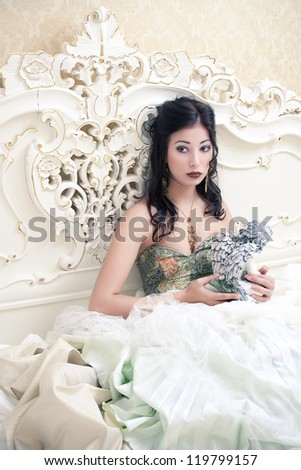 Vintage portrait of a beautiful queen like girl in the white bedroom holding a cupid statuette. Retro style. Studio shot