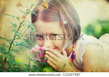 Vintage portrait of a cute little girl smelling a flower