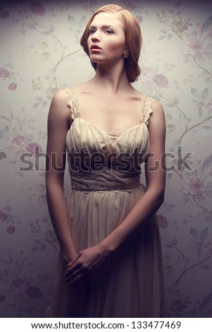 Vintage portrait of a glamorous doll-like retro girl posing in gorgeous classic dress . Hollywood style (film noir). Perfect skin and hairdo. Studio shot
