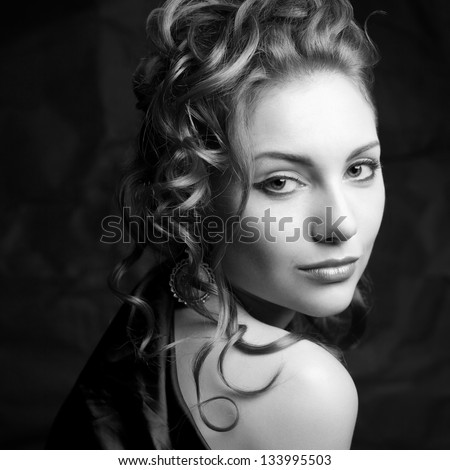 Vintage portrait of a glamorous queen-like young woman posing over wrinkled black paper background. Retro (Hollywood) style. Film noir. Old classic movie. Black and white (monochrome) studio shot