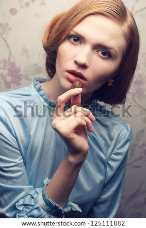 Vintage portrait of a glamorous red-haired (ginger) girl in blue dress eating chocolate candy. Studio shot