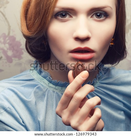 Vintage portrait of a glamorous red-haired (ginger) girl in blue dress eating chocolate candy. Close up. Studio shot