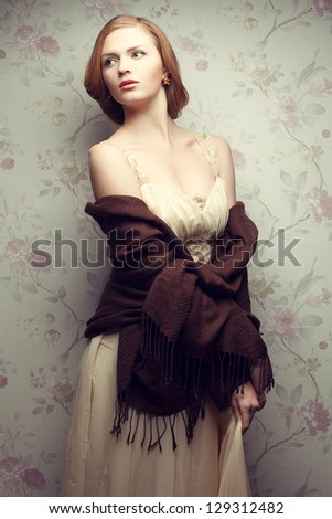 Vintage portrait of a glamorous red-haired (ginger) girl posing in great beige dress. Studio shot