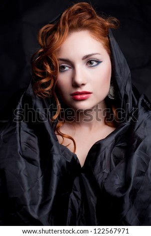 Vintage portrait of a glamorous red-haired queen like girl over wrinkled black paper background. Retro style. Studio shot