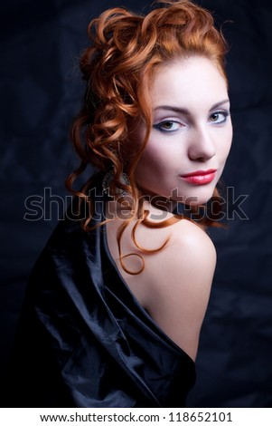 Vintage portrait of a glamourous queen like girl over wrinkled black paper background. Retro style. Studio shot