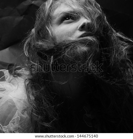 Vintage portrait of a gorgeous queen-like girl posing over wrinkled black paper background. Retro (classic) style. Close up. Studio shot