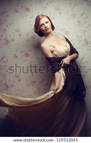 Vintage portrait of a happy glamorous red-haired (ginger) girl dancing in great beige dress and having fun. Studio shot