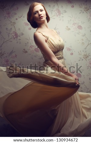 Vintage portrait of a happy glamorous red-haired (ginger) girl posing in great flying beige dress and dancing. Retro style. Studio shot