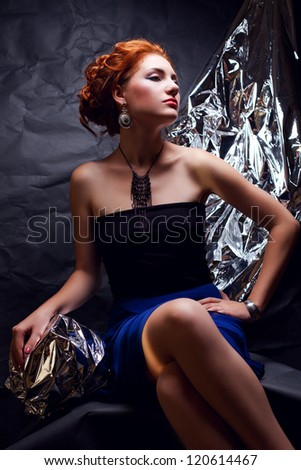 Vintage portrait of a seductive ginger model with silver foil posing over wrinkled black paper background. studio shot