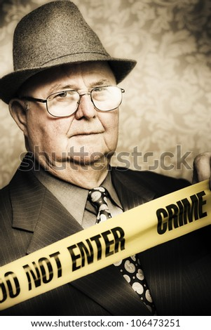 Vintage portrait of an elderly perceptive crime detective with an observant look in his eye watching carefully as he stands behind the tape at a crime scene