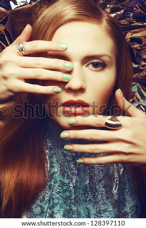 Vintage portrait of beautiful red-haired woman with long healthy shiny hair, perfect makeup and stylish silver accessories on her hands posing over wrinkled foil background. Retro-futurism.