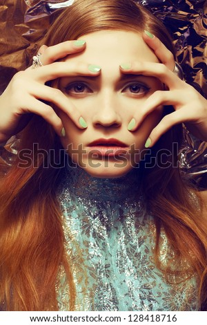 Vintage portrait of beautiful red-haired woman with long healthy shiny hair, perfect makeup and stylish silver accessories on her hands. Hands on face. Close up. Retro-futurism.