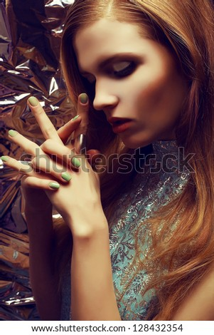 Vintage portrait of beautiful red-haired woman with long healthy shiny hair, perfect makeup and stylish silver accessories on her hands. Hands on face. Close up. Profile. Retro-futurism.