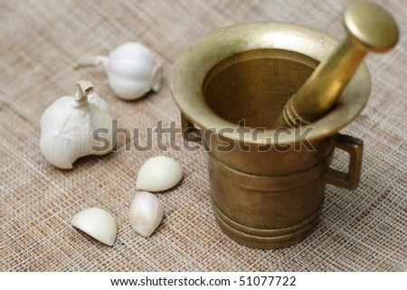 Vintage pounder with garlic pieces. Shallow depth of field with focus on garlic.