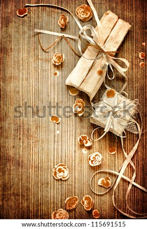 Vintage Present,gift bow with petal from flowers on wooden table/valentin day background