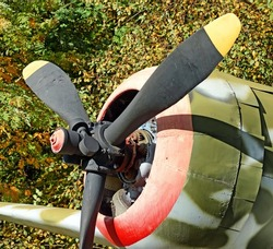 vintage prop driven engine military fighter aircraft in camouflage front close up view with airplane parts nose fuselage propeller detail exterior transportation war patriotic technology theme scene