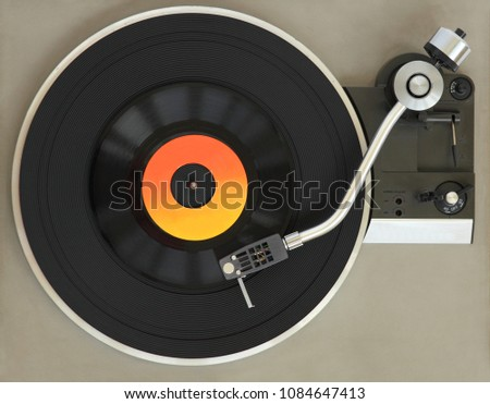 Vintage record player with vinyl record.  #1084647413
