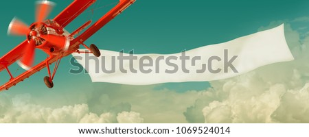 Vintage red airplane flying in the sky with a white blank banner