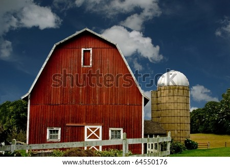 vintage red barn and silo with a white fence against a blue sky