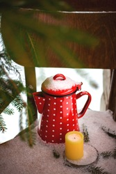 Vintage red coffee or tea pot with candle under the snow on the old chair. Rustic catle