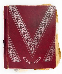 Vintage red cover scrapbook with yellowed frayed pages.