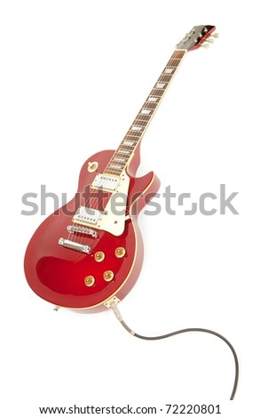 Vintage red electric solid body guitar plugged in with instrument cable in its sides jack. Isolated on white.