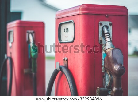 Vintage red gasoline pumps outside of an old gas station.