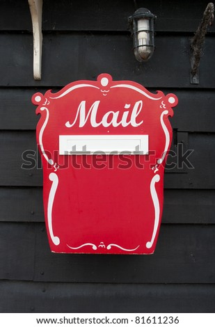 vintage red mailbox against a wooden wall