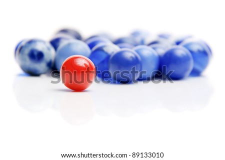 Vintage red marble with standing out of a crowd of blue marbles isolated on white