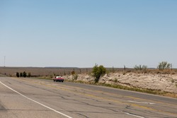 Vintage Red Muscle Car Drives On Desert Highway Into Distance Near Marfa Texas