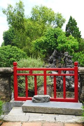 Vintage red painted wooden gate with tree covered island rock garden behind and ancient carved stone artifact on the ground in front