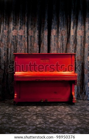 Vintage red piano in dark theater or nightclub interior over floral ornate curtains background