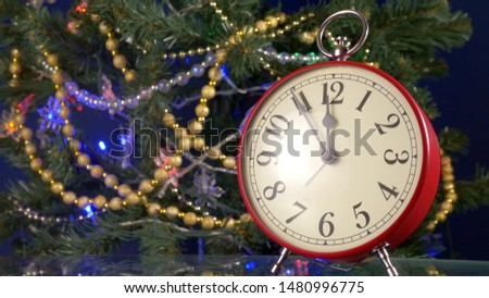 Vintage red retro alarm clock on the background of the Christmas tree, from five minutes to midnight, copy space for your text