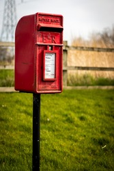 Vintage red Royal Mail post box on green grass background, made in Scotland