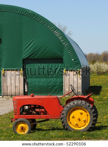 Vintage red tractor at a green barn