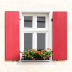 vintage red wooden window exterior with flower bed outside
