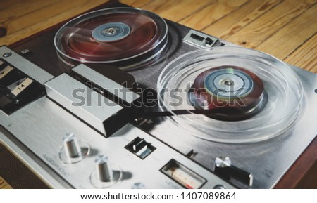 Vintage reel to reel tape recorder on a wooden floor #1407089864