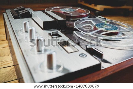 Vintage reel to reel tape recorder on a wooden floor #1407089879