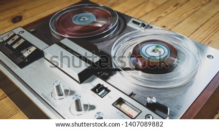 Vintage reel to reel tape recorder on a wooden floor #1407089882